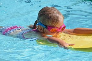 Image is a young girl in goggles learning to swim.