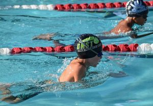 Image is of two boys swimming competitively in a pool.